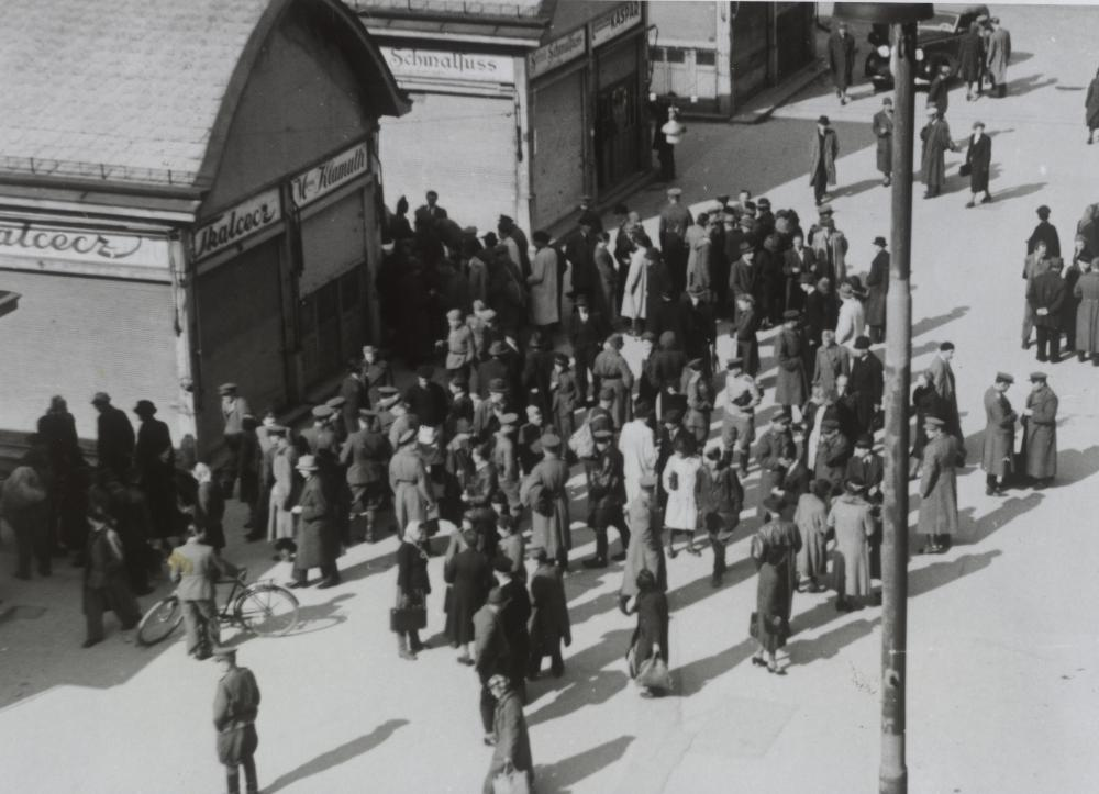 """Waren konnte man nur noch mit Bezugsscheinen bekommen, in Geschäften konnte man also nicht unbeschränkt einkaufen. Daneben florierte in der Stadt der Schwarzmarkt und am Land der illegale Tausch von Wertgegenständen gegen Lebensmittel (""""Hamstern""""). Diese Aufnahme, die viele sowjetische Soldaten an einem Treffpunkt für verbotenen Tauschhandel zeigt, wurde vom Fotografen als Razzia beschrieben."""