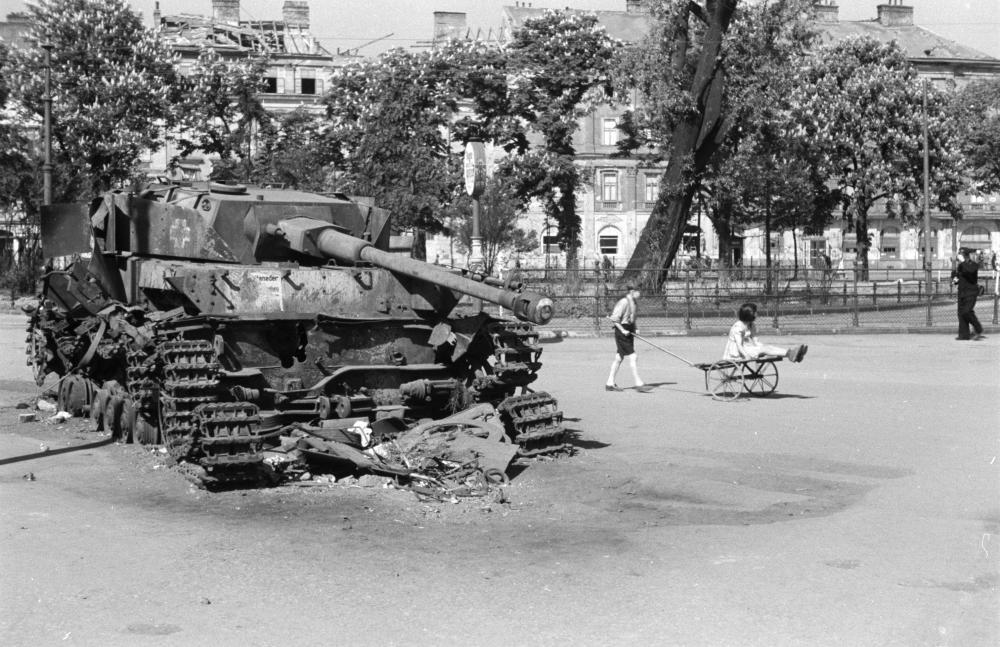 Der Fotograf inszeniert hier die Gleichzeitigkeit von Gewalt und Alltag. Die Kinder neben dem Panzer sind aber auch Symbole für die Überwindung des Kriegs und den Neubeginn.