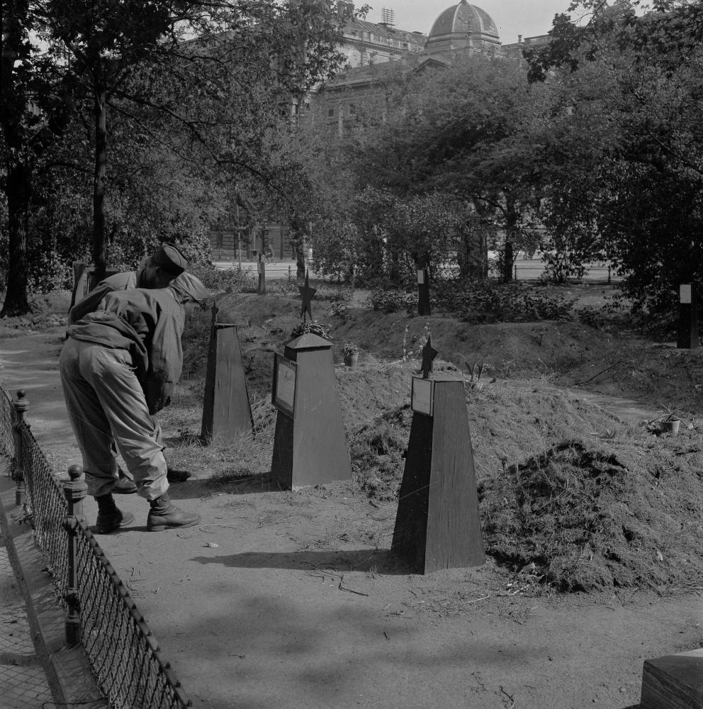 """Dieses Foto zeigt US-Soldaten beim Betrachten von Gräbern sowjetischer Soldaten in der US-verwalteten Zone Wiens. Die Aufnahme betont den gegenseitigen Respekt im beginnenden """"Kalten Krieg""""."""